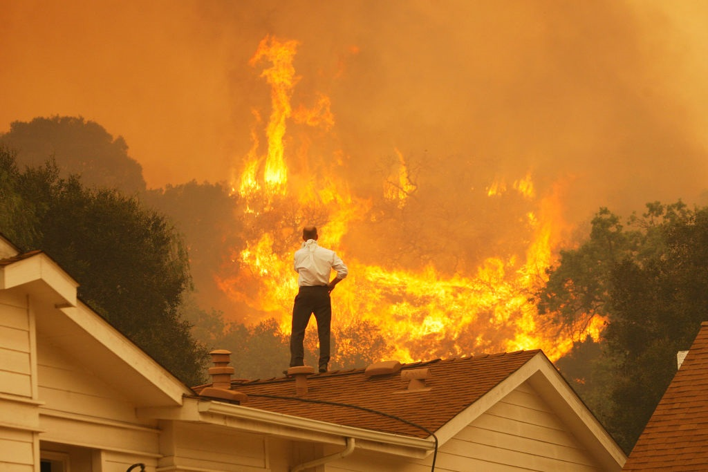 A man on a rooftop looks at approaching flames as the Springs fire continues to grow on May 3, 2013 near Camarillo, California.   (Photo by David McNew/Getty Images)