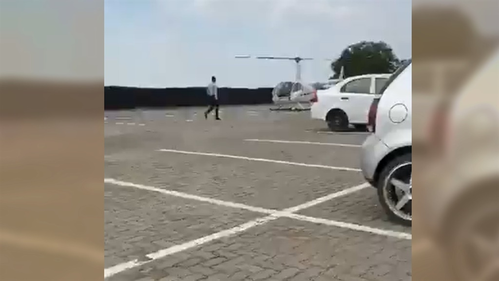 A NWU student walking towards the helicopter to fetch his backpack.