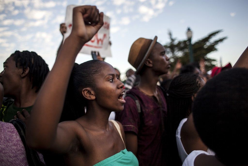 Students cheer after the Cecil Rhodes statue was removed from the University of Cape Town on April 9, 2015 in Cape Town, South Africa. The statue of British colonialist Cecil John Rhodes was removed from the University of Cape Town as a result of a month long protest by students citing the statue great symbolic power which glorified someone who exploited black labour and stole land from indigenous people. (Photo by Charlie Shoemaker/Getty Images)