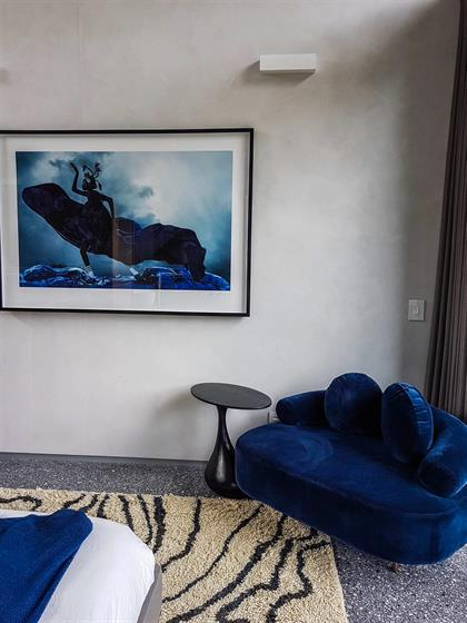 lounge with blue chair and photo