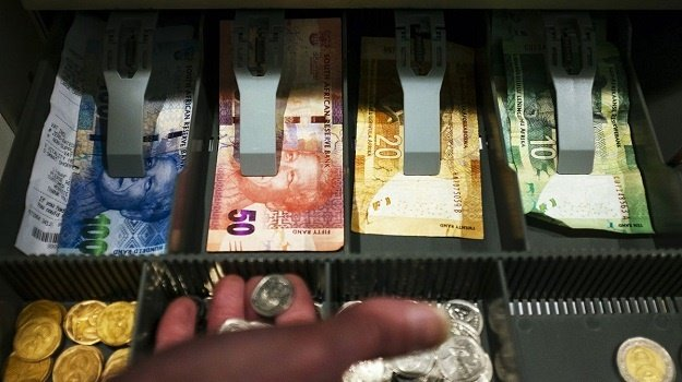 South African rand banknotes and coins sit in the
