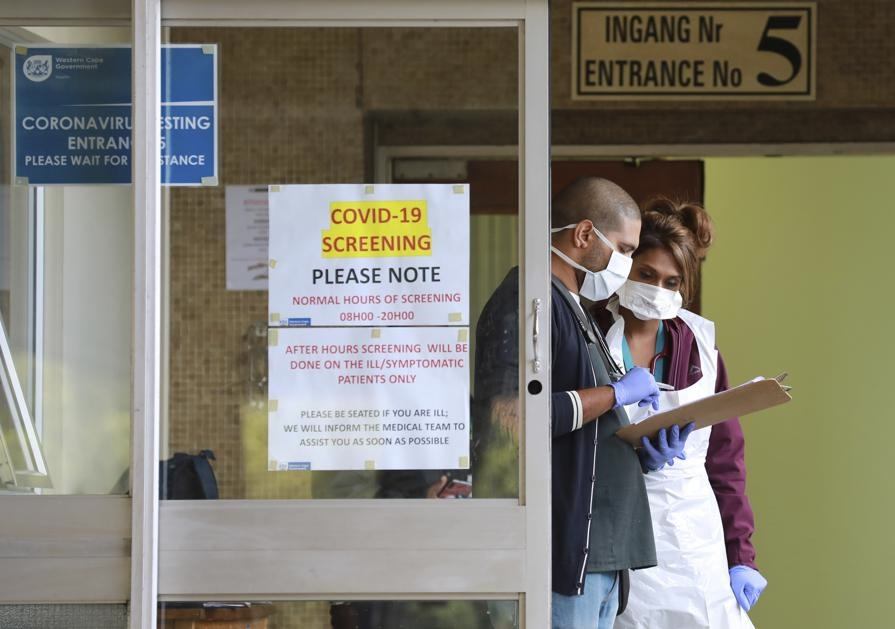 Medical workers check a file at a testing centre at Tygerberg Hospital in Cape Town. Picture: Nardus Engelbrecht/AP