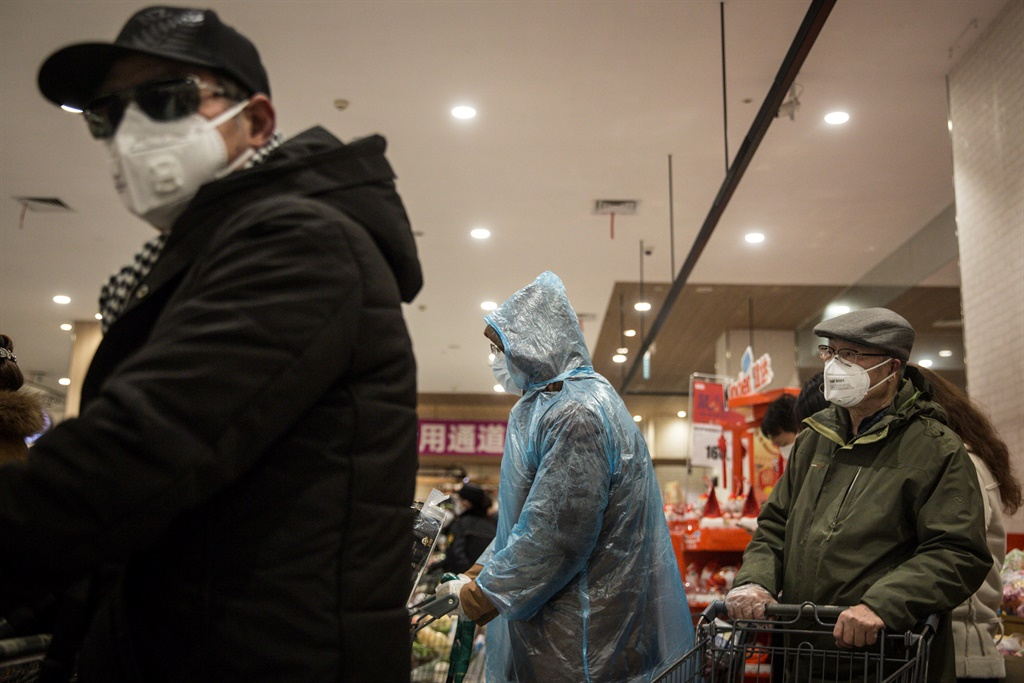 Residents wear protective clothes and mask as they line up to pay in the supermarket on February 12, 2020 in Wuhan, Hubei province, China. Flights, trains and public transport including buses, subway and ferry services have been closed for 21 days. The number of those who have died from the Wuhan coronavirus, known as 2019-nCoV, in China climbed to 1117.  (Photo by Stringer/Getty Images)