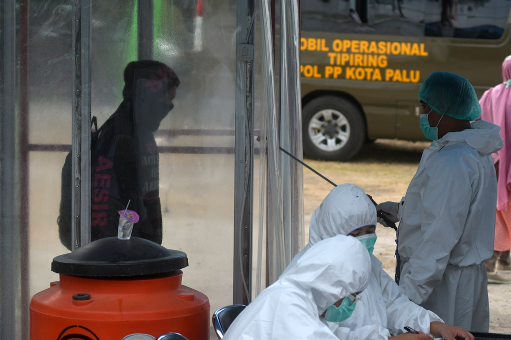 Health workers spray germ-killing liquid into the