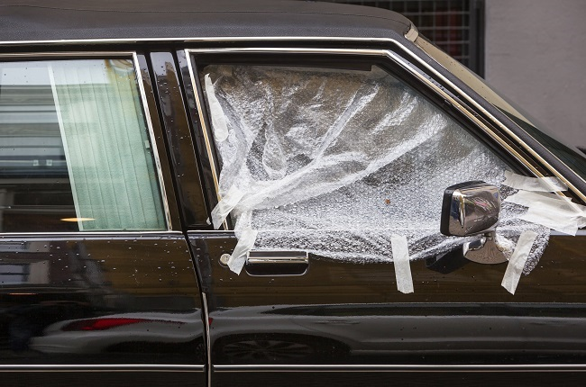 Broken car window covered with plastic in Rotterda