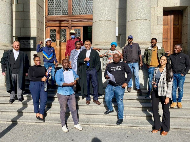 Empolweni residents, legal representatives, and community activists from Khayelitsha CAN outside the Western Cape High Court which ruled that residents whose shacks were demolished can return to the land. (Photo: Zacharia Mashele, GroundUp)