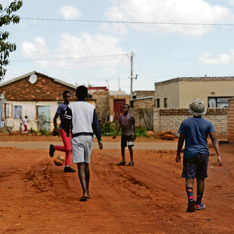 Children continue to play football outside during day 20 of the national lockdown in Orange Farm. Picture: Tebogo Letsie