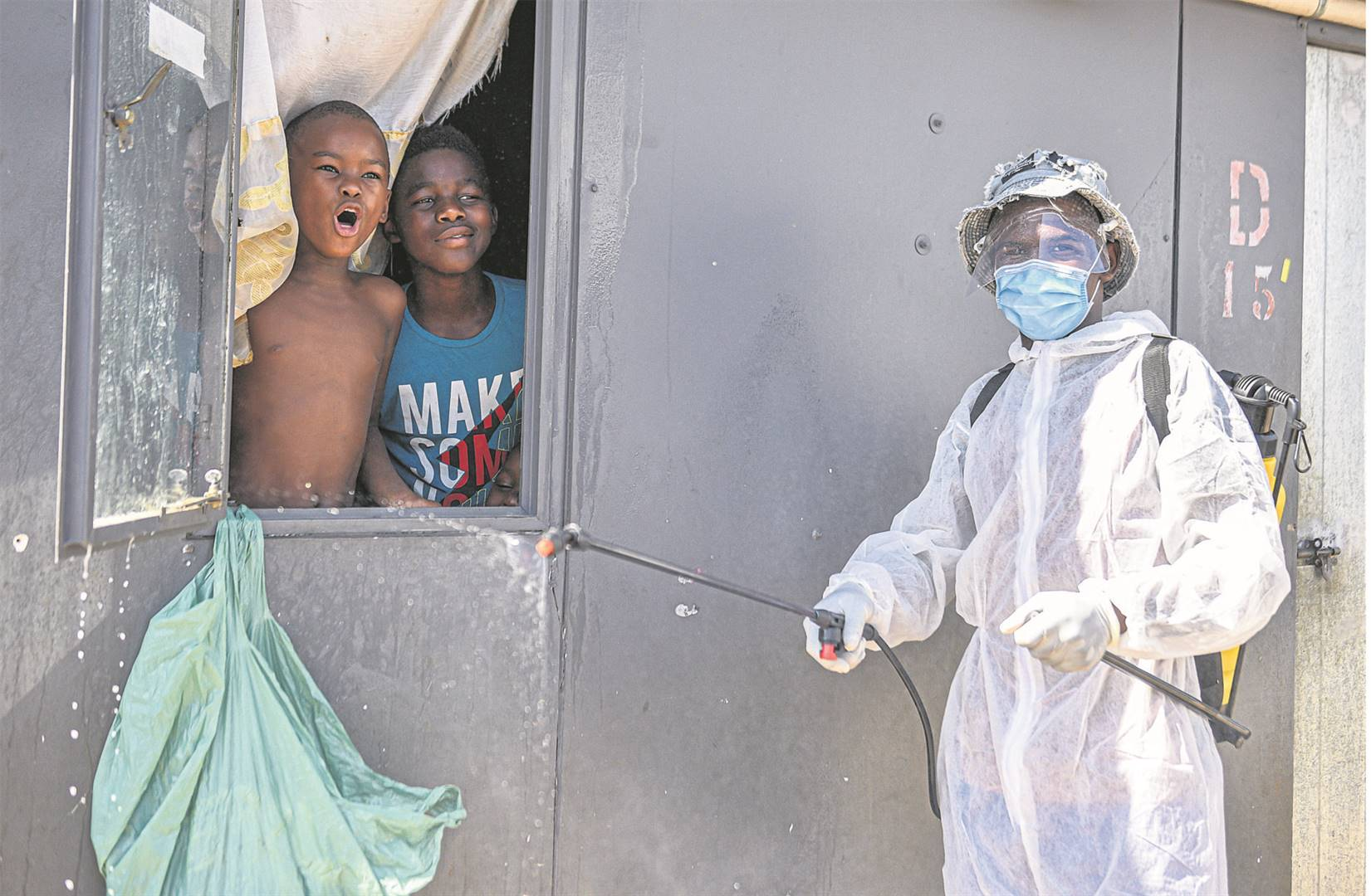ABOVE: Children from Jika Joe cheer while Tsosang Maketela sanitises their home yesterday.LEFT: City mayor Mzimkhulu Thebolla (second from left) and KZN Finance MEC Ravi Pillay (front) led the sanitisation drive at the Jika Joe informal settlement and other three areas yesterday.PHOTOS: moeketsi mamane