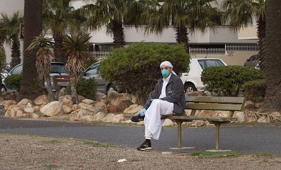 A Muslim cleric sits on a bench of the usually busy Sea Point Promenade in Cape Town before joining a small group of clerics (not visible) gathering to look out for the crescent moon which will signal the start of the month of Ramadan. (Rodger Bosch, AFP)