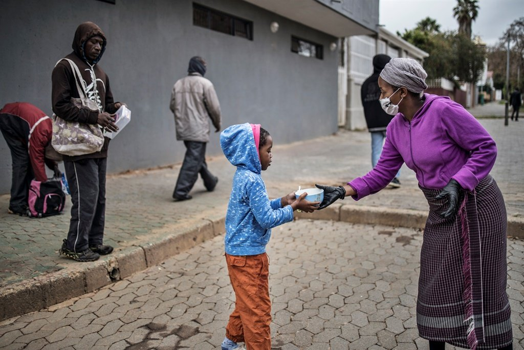 A volunteer for the grassroots charity, Hope for Vrededorp, hands over a warm meal to a child at a daily food distribution in the impoverished district of Vrededorp in Johannesburg as the country remains under lockdown.