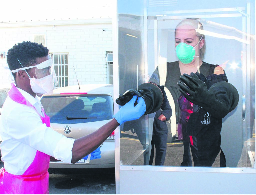 A clinician from Gugulethu Community Health Centre receiving a test swab from her assistant nurse.