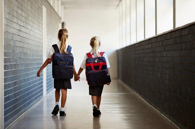 Schoolgirls walking hand in hand. (PHOTO: Klaus Vedfelt/Getty Images)