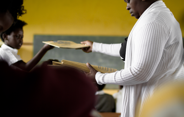 Teacher handing out books (PHOTO:GETTY IMAGES)