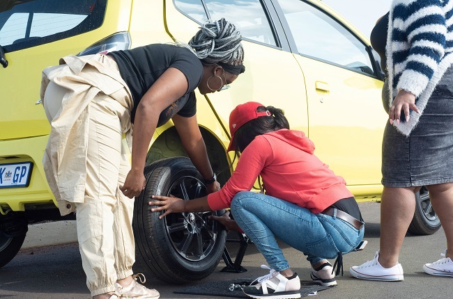 Females changing a tyre on a Toyota Agya