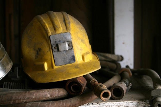 A yellow mining helmet on a pile of old hose.