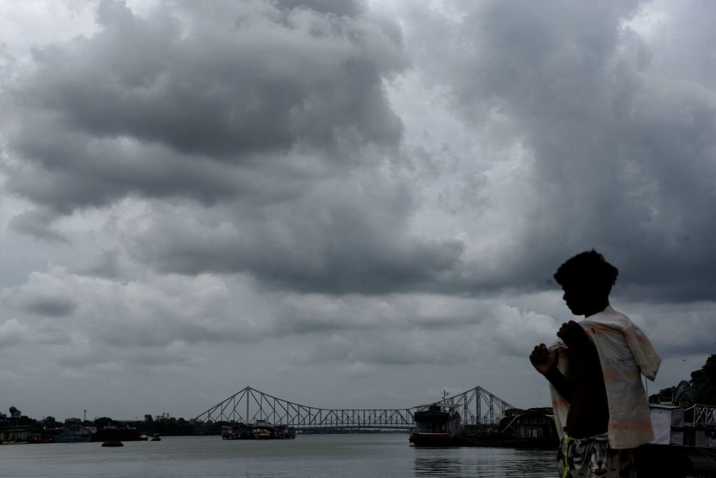 A man looks on as dark clouds hover over Howrah Bridge in Kolkata, India.  Cyclone Amphan likely to make landfall on Wednesday. (Samir Jana/Hindustan Times via Getty Images)