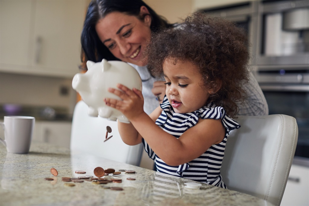 Mother and toddler girl getting money out of a piggy bank. (PHOTO: Sally Anscombe for Getty Images)