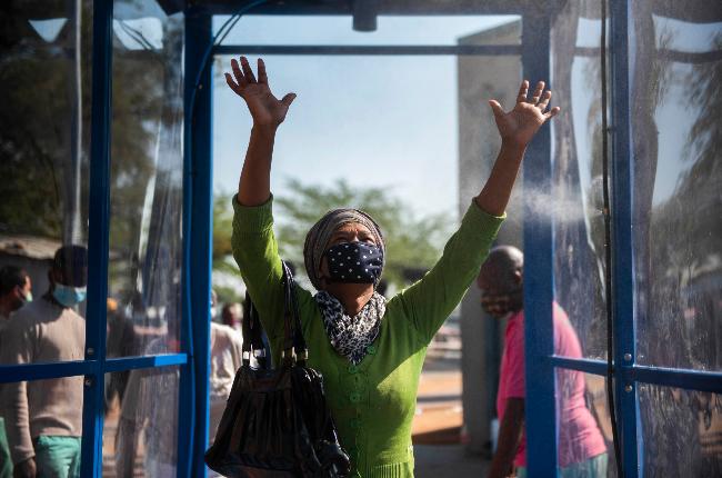 Woman going through a sanitising booth (PHOTO: Alet Pretorius/Gallo Images)