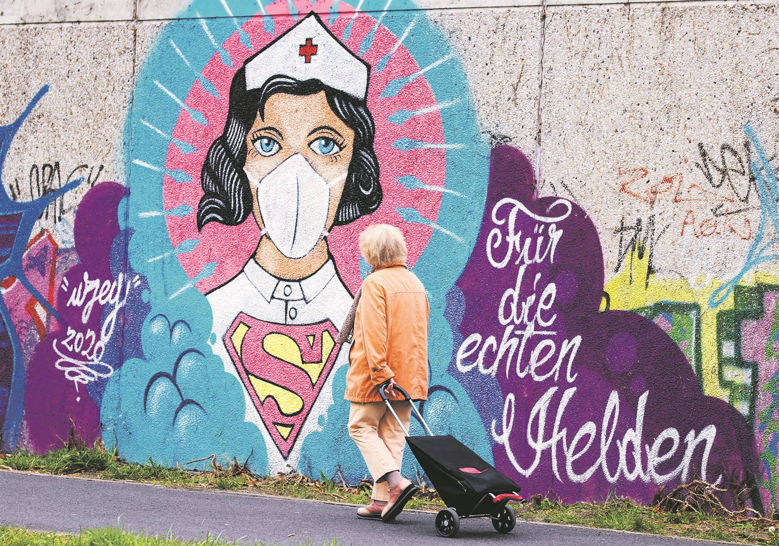 A woman walks past street art painted by German artist Kai 'Uzey'Wohlgemuth in Hamm, Germany, where more than 130 000 cases of the Covid-19 coronavirus have been confirmed, with more than 3 000 deaths and 57 000 recoveries. Picture: Lars Baron / Getty Images