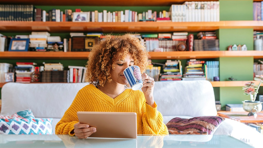 Young woman with curly hair using tablet and drink