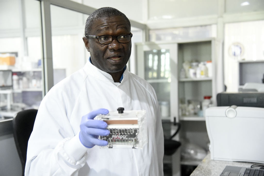 Professor Christian Happi holds a minipcr thermal cycler, a laboratory apparatus used to amplify segments of DNA during an inspection of facilities at the centre located at the Redeemer's University.