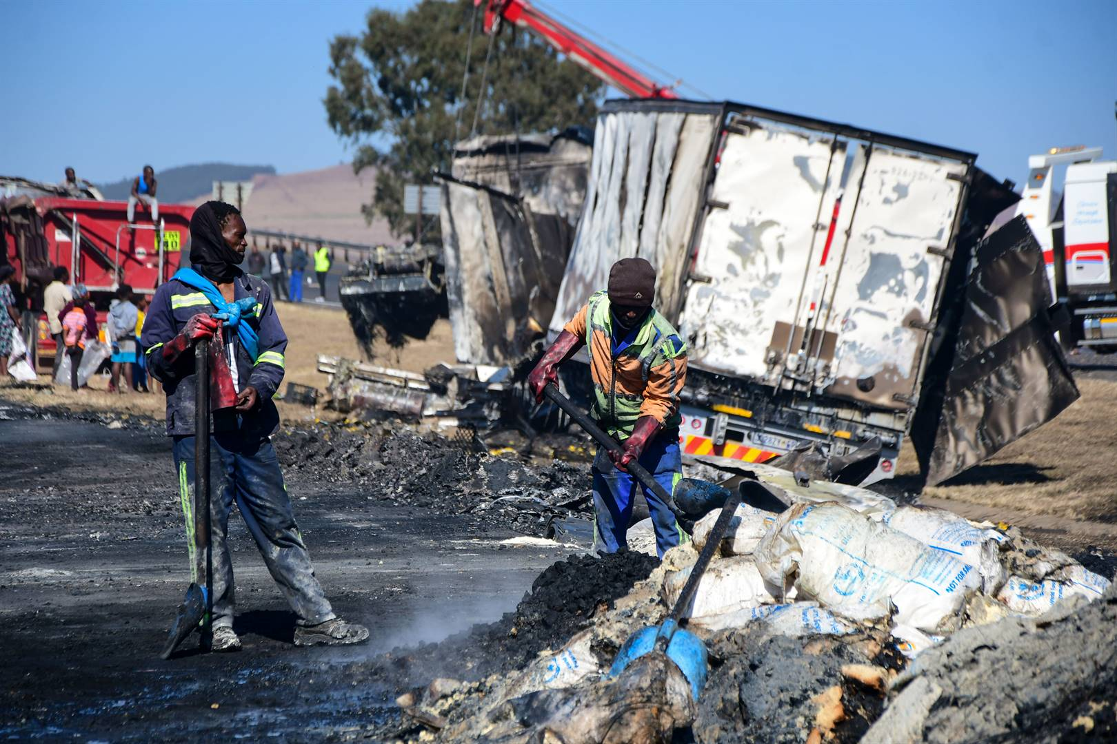 Workers clear the rubble from a burnt truck on the N3 near the Mooi River Plaza earlier this week. Picture: Darren Stewart/Gallo Images
