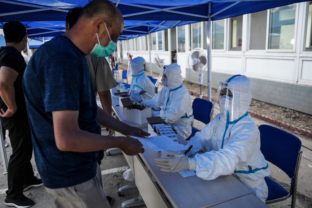 A man (L) registers to undergo a swab test for the coronavirus at a testing centre in Beijing.