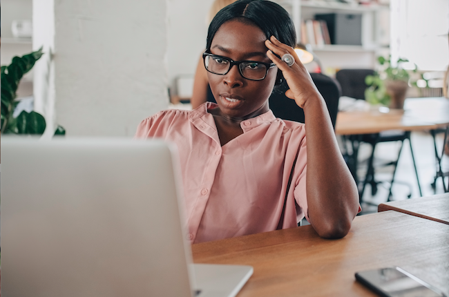 Woman stressed looking at laptop