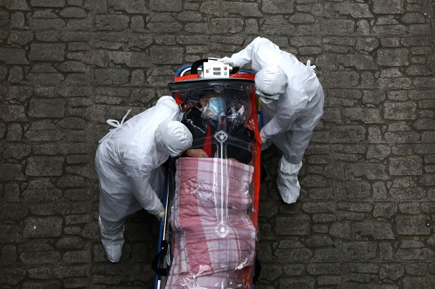 Medical staff, wearing protective gear, move a patient infected with the coronavirus from an ambulance to a hospital in Seoul, South Korea.