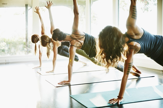 Group of women practicing yoga in side plank pose