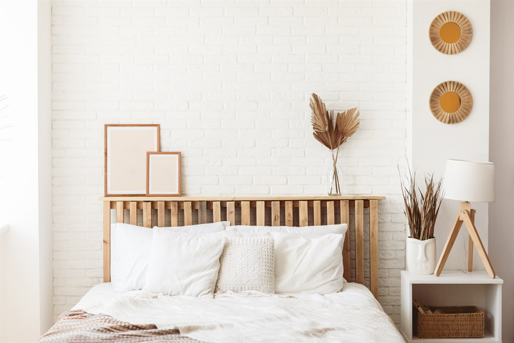 Wooden headboard with dry gold palm leaves in a gl