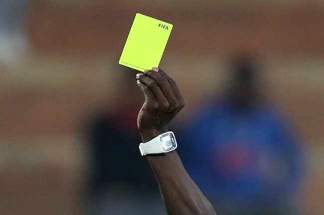 A referee issues a yellow card (Gallo Images)