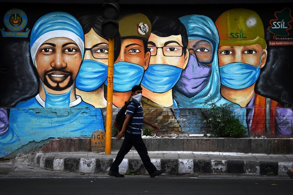 A man walks past a mural of frontline workers in New Delhi.