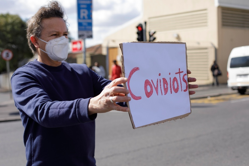 Healthcare worker holds up a sign aimed at anti-va