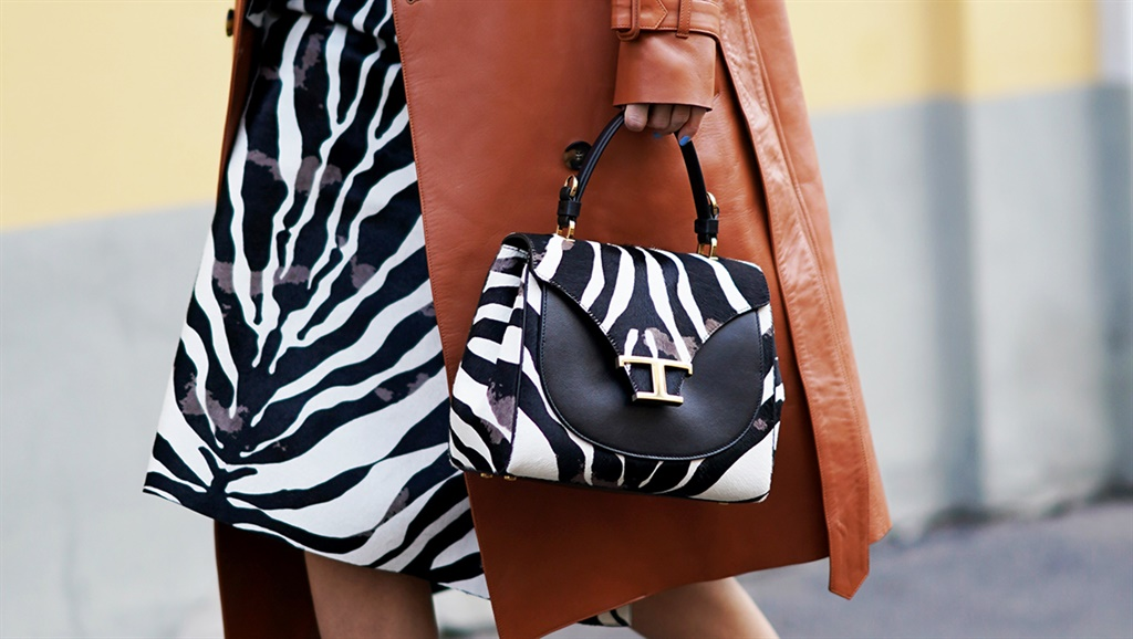 A guest wears a black and white zebra print Tods bag outside Tods, during Milan Fashion Week Fall/Winter 2020-2021 in Milan. Photo by Edward Berthelot/Getty Images