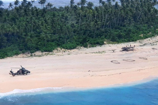 The SOS message on a beach that drew a search party's attention to three stranded men.  (Photo: Australian Defense Force)