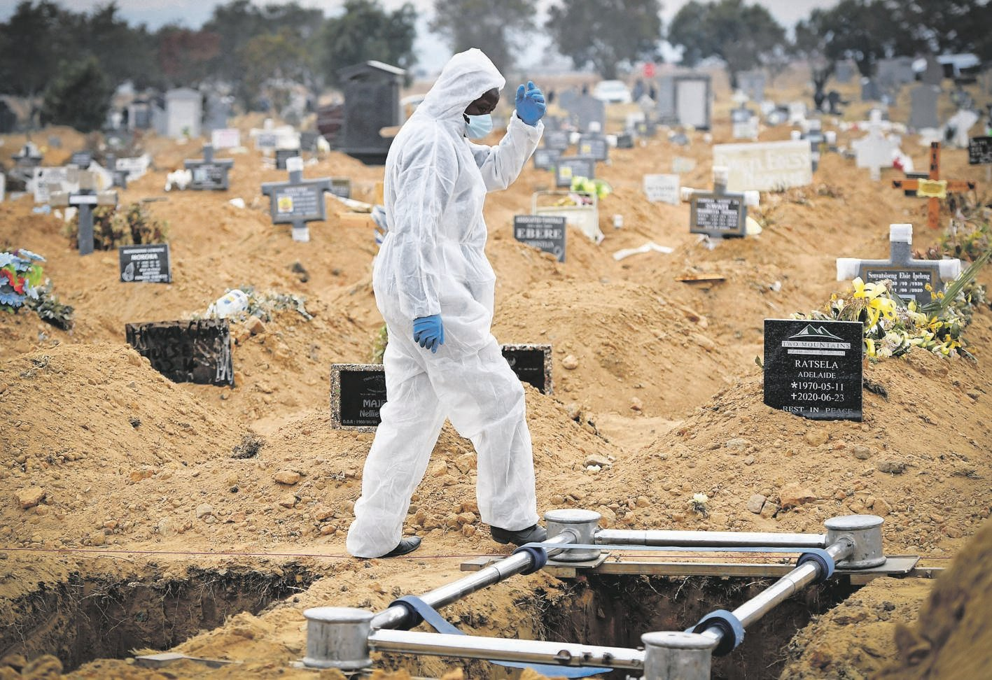 Funeral parlour staff, in personal protective gear, prepare a grave for a Covid-19-related death      Picture: Felix Dlangamandla