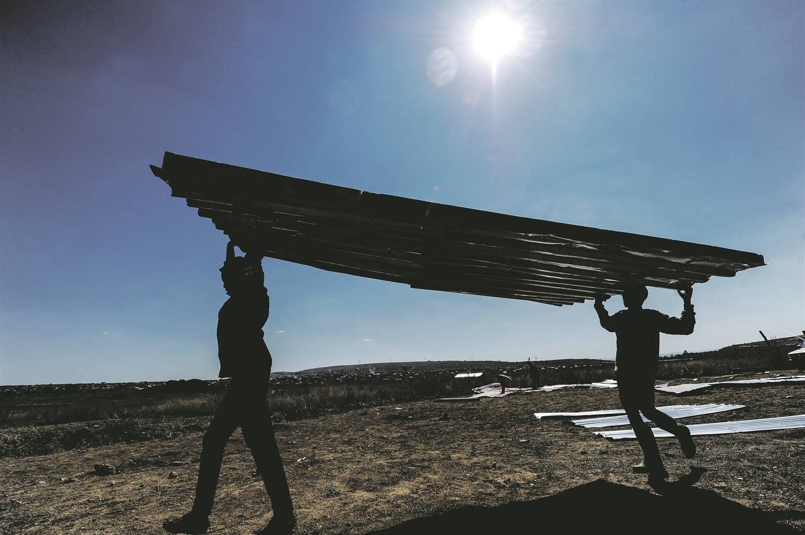 Residents of Lakeside View informal settlement in Lawley, south of Johannesburg, carry corrugated iron sheets to rebuild their shacks after they were demolished by the Red Ants. Picture: Rosetta Msimango