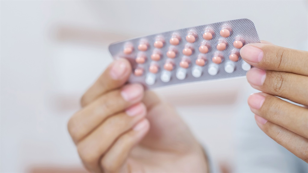 Woman hands opening birth control pills in hand. E