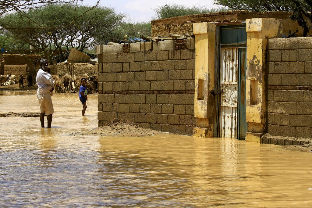 A Sudanese man stands in flood water, after torrential rain led to landslides and flash floods, in the town of Umm Dawan Ban, southeast of the capital Khartoum on August 2, 2020.