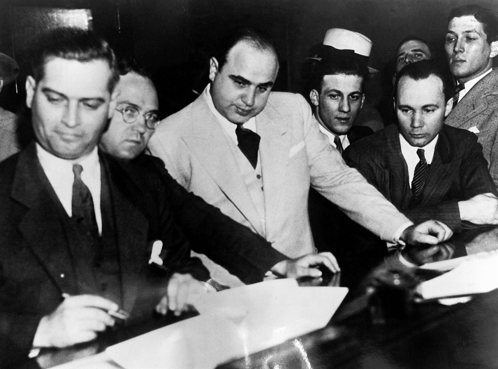Al Capone, the gangster and so-called ruler of the Chicago underworld, signs a Bail Bond, signalling the beginning of his prosecution for failure to pay significant income tax. To the left of the picture are Dwight H. Green and Samuel G. Clawson, the two prosecuting Assistant US Attorneys who claim that their case is watertight. Picture: Hulton-Deutsch/Hulton-Deutsch Collection/Corbis via Getty Images