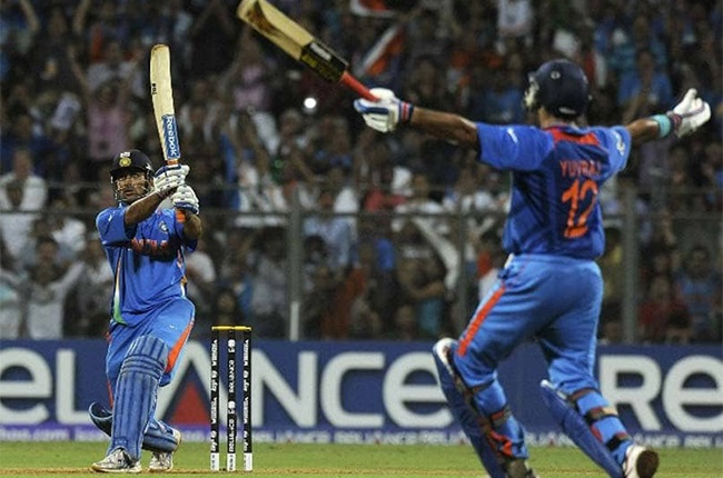Indian captain Mahendra Singh Dhoni (L) hits a six to win against Sri Lanka as teammate Yuvraj Singh reacts during the Cricket World Cup 2011 final at The Wankhede Stadium in Mumbai on April 2, 2011. India beat Sri Lanka by six wickets.
