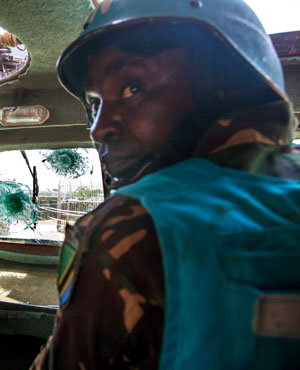 UNAMID military personnel from Tanzania, based in South Darfur, driving one of their APCs that was damaged after being ambushed in an attack that killed seven peacekeepers. (Albert Gonzalez Farran, AFP)