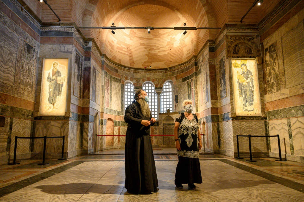 A priest (L) and a woman visit the Chora or Kariye Museum, formerly the Church of the Holy Saviour, a medieval Byzantine Greek Orthodox church, on August 21, 2020, in the Fatih district in Istanbul.