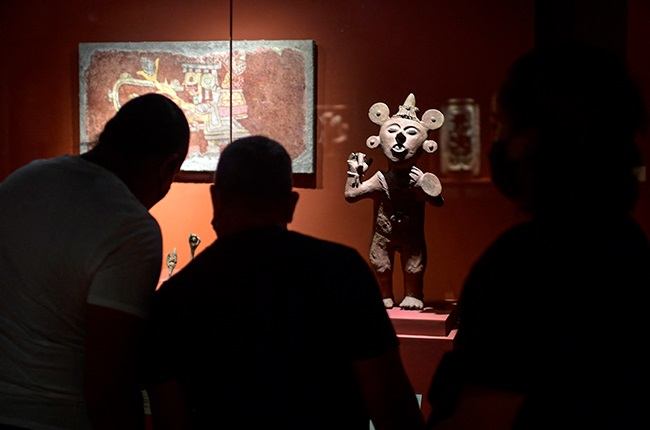 Visitors look at the work titled