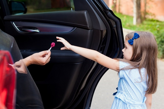 Stranger in the car offers lollipop to the child. Act fast and help the child in need. Getty Images.