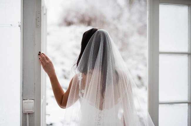 The bride was accompanied by a priest and a woman in a bridesmaid dress and heels, holding a bouquet of flowers. (Photo: Gallo Images/Getty Images)