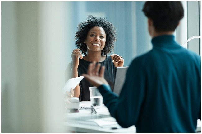 Woman speaking to a colleague at work.