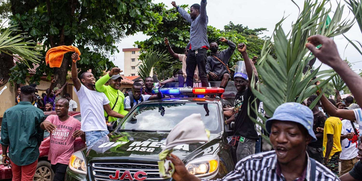 Protesters stand on a vehicle that is part of a military convoy sent to enforce the curfew at the Lagos State Secretariat, Alausa, in Nigeria on October 20, 2020.