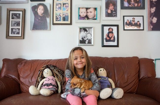 Nicela Naudé is now a happy six-year-old. Here she is with her dog, Dobby. (Photo: Misha Jordaan)
